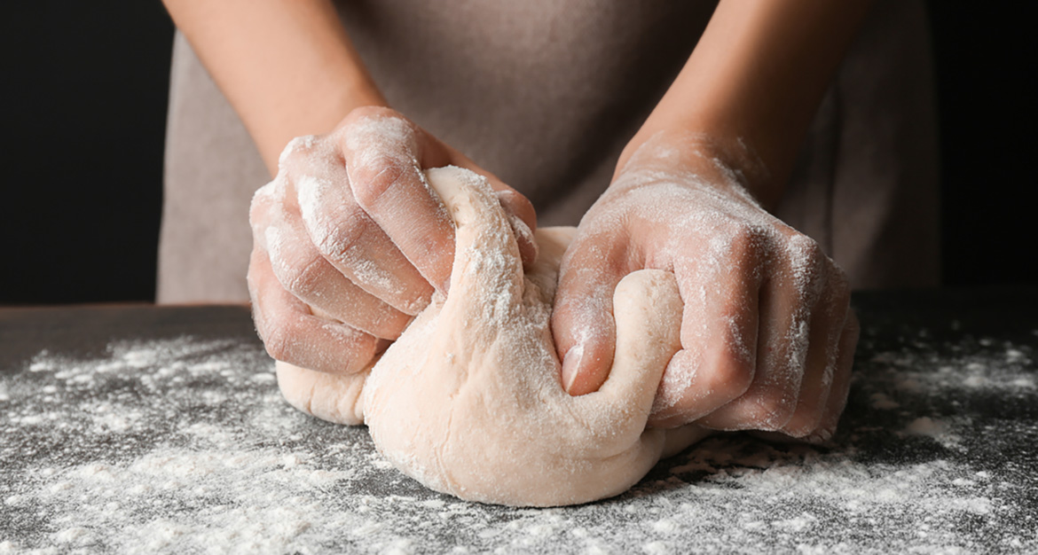 person making fresh pizza dough by hand