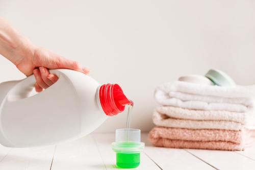 closeup hand pouring liquid detergent